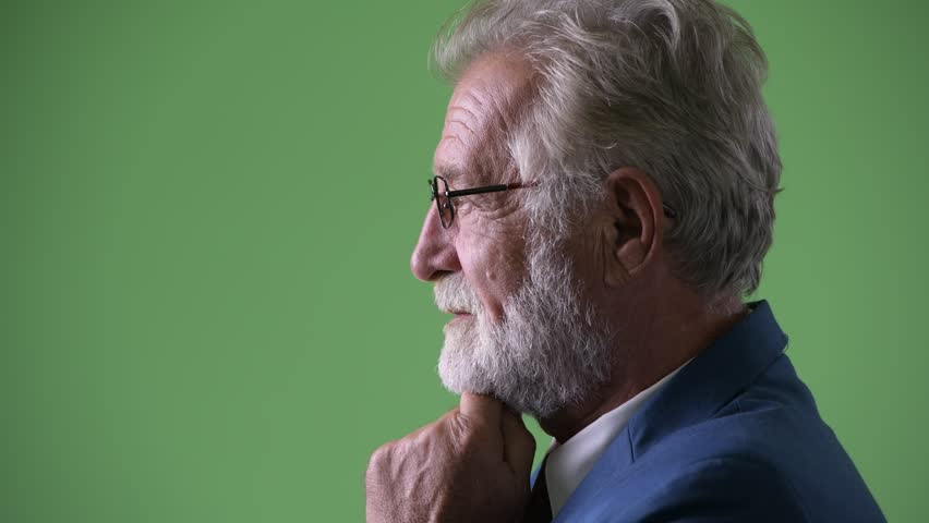 Handsome senior bearded businessman against green background #1014687113
