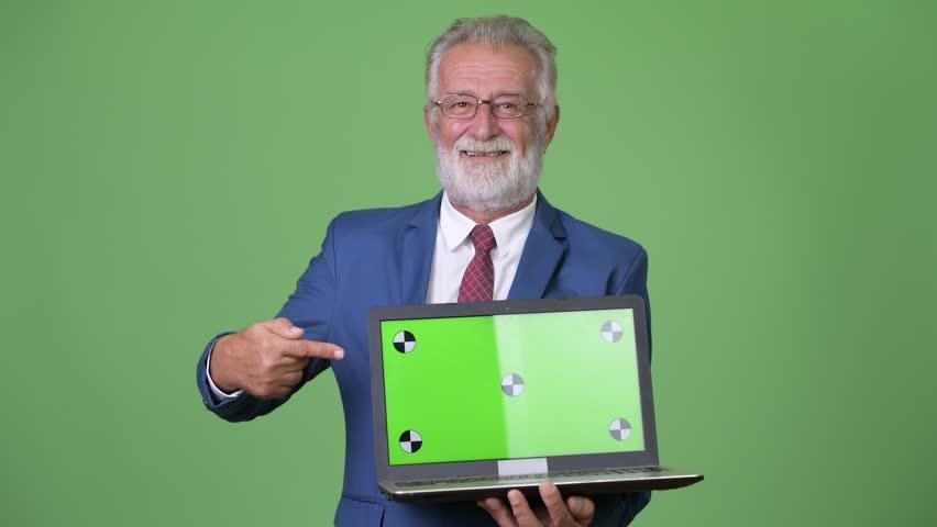 Handsome senior bearded businessman against green background | Shutterstock HD Video #1014687143