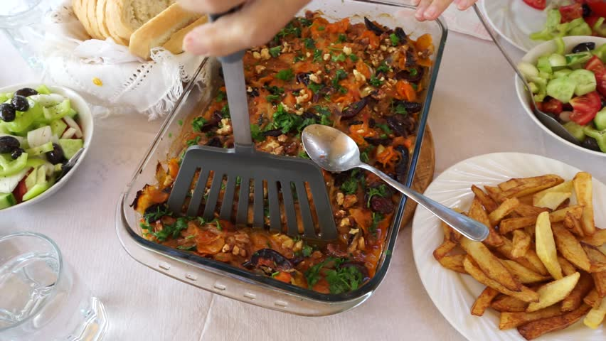 Traditional for Albania dish with koran (Ohrid trout), vegetables and walnuts served on the table for lunch with salads, French fries and bread. The process of serving on the plates in Lin village.