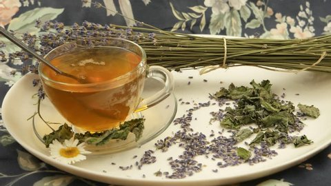 The cup of herbal tea on a white dish and a bouquet of dry lavender  against a background of fabric with a floral pattern, a floral arrangement