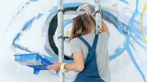 Graffiti Artist Drawing face of beautiful woman and eye with paint on Street Wall. Female working with brush. Urban Outdoors Art Concept. Slow motion.