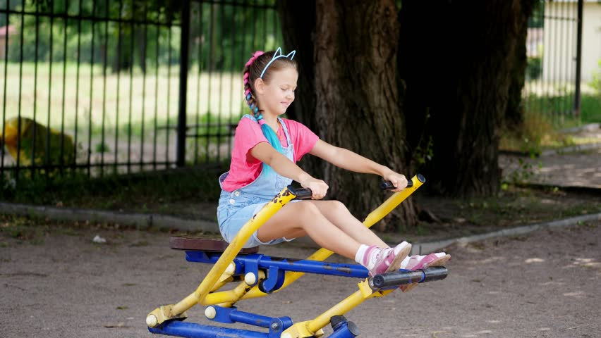 Smiling, happy eight year old girl engaged, doing exercises on outdoor exercise equipment, outdoors, in the park, summer, hot day during the holidays.