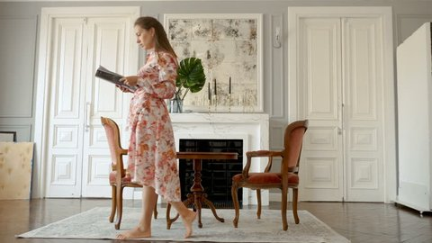Young woman in colorful dress is reading magazine while walking around the room