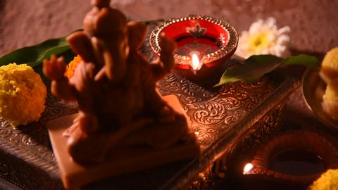 diwali diya with flower rangoli, sweets and gifts