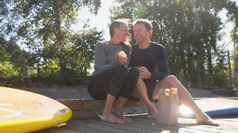 Handheld shot of couple having food while sitting on pier