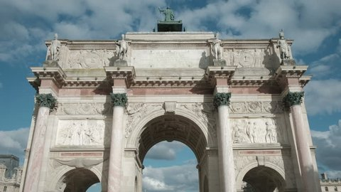 Forward dolly push in low angle view of centered Arc de Triomphe du Carrousel in Paris, France