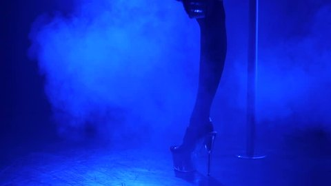 Slender legs of pole dancer in high heels, close-up. Close-up of stripper shoes in the club. Pole dance.