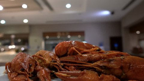 Point of view. The waiter carries a plate of crayfish in the restaurant's hall. Concept of luxury recreation and eating at an expensive resort.