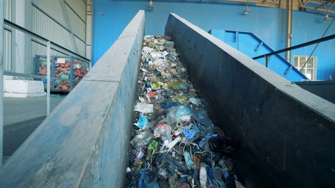 Conveyor belt filled with trash is moving upwards. Environmental pollution concept.