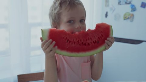 Happy Boy Appetizing Eating Red Watermelon And Juice Flowing Under The Teeth
