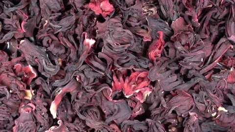 Large leaves of hibiscus red dry tea background, close up. Loop rotation. Front of the camera rotates plate with hibiscus red dry tea, macro