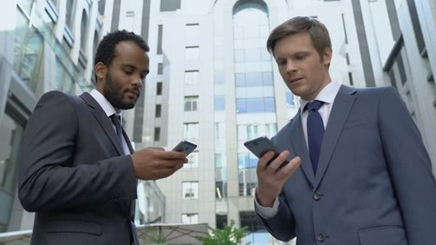 Two businessmen using smartphones, exchanging contacts, profitable acquaintance