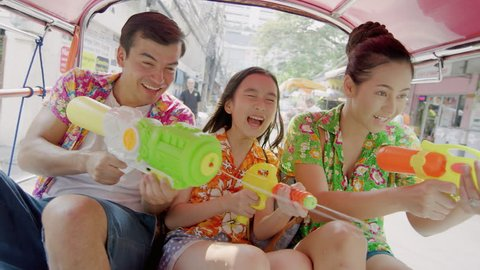 Asian family with daughter in tuk tuk taxi with water squirt guns, splashing water during a water fight as part of the annual Songkran Festival in Thailand Bangkok. Slow motion hand held.