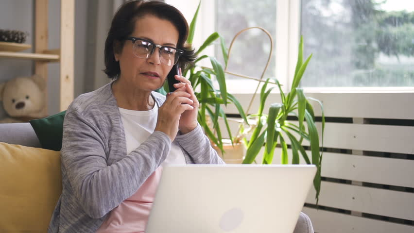 Mature businesswoman is talking on phone, using laptop sitting at home, beautiful seniora is making call with silvery pc on lap, typing on sofa in cozy apartment with daylight. Concept: working | Shutterstock HD Video #1014879343