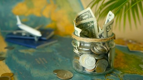 Travel budget concept. Money saved for vacation in glass jar with world map, passport and plane. Banknotes and coins for adventure. Savings for journey. Collecting money for trip. Moneybox with cash.