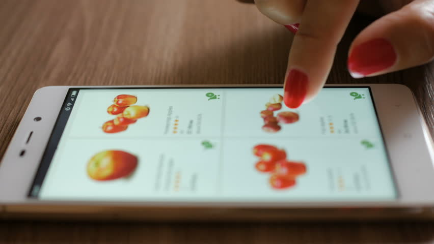 Woman orders food home in an online store using a smartphone. Female selects the fruit apples in the grocery online store.  Close-up. 4K UHD. Screen is blurred