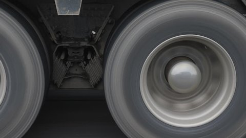 Closeup of truck wheels and tires with suspension. Passing truck on highway.