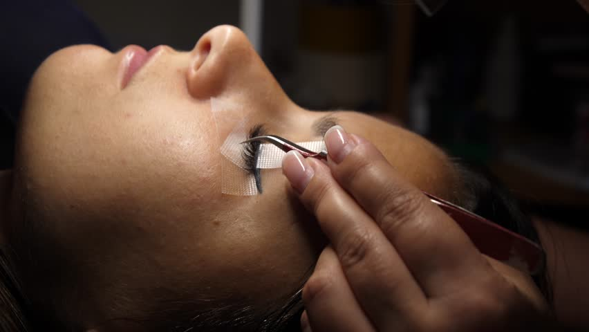 Woman eye with long eyelashes. Eyelash extension. Gluing artificial eyelashes with tweezers. A woman lies on a cosmetic procedure. movement of the camera.