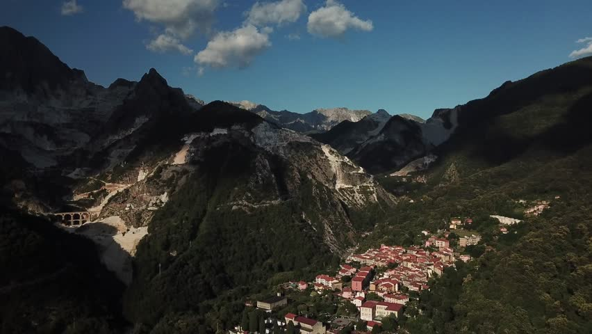 Aerial: Flying above Roman viaduct and the village of Bedizzano at the world famous marble quarry near the city of Carrara, Tuscany, Italy