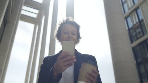 Panning medium shot of middle aged woman with short hair wearing smart casual clothes standing among columns with takeaway coffee cup in her hand and texting on phone, low angle view