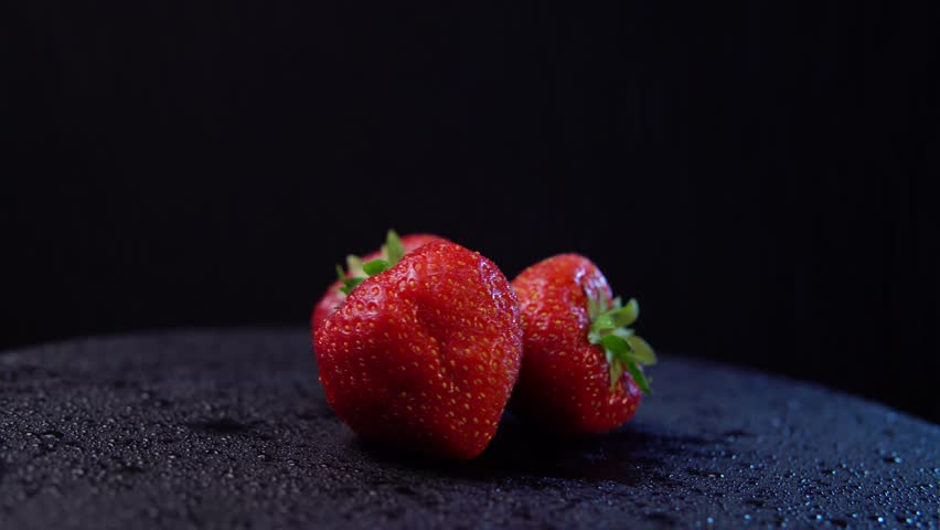 Fresh, ripe juicy strawberries with drops of water revolve. Red berry counterclockwise rotation, close-up. Strawberry background, seamless looping.