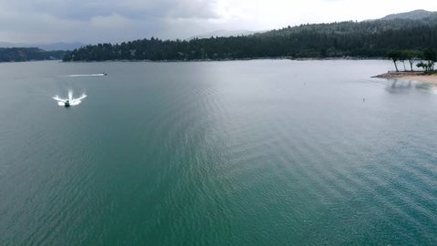 Aerial Shot Flying Over Lake Arrowhead with a Boat Traveling Across the Shot