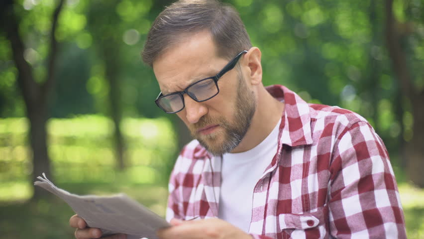 Aging man in eyeglasses trying to read newspaper in park, farsightedness, myopia