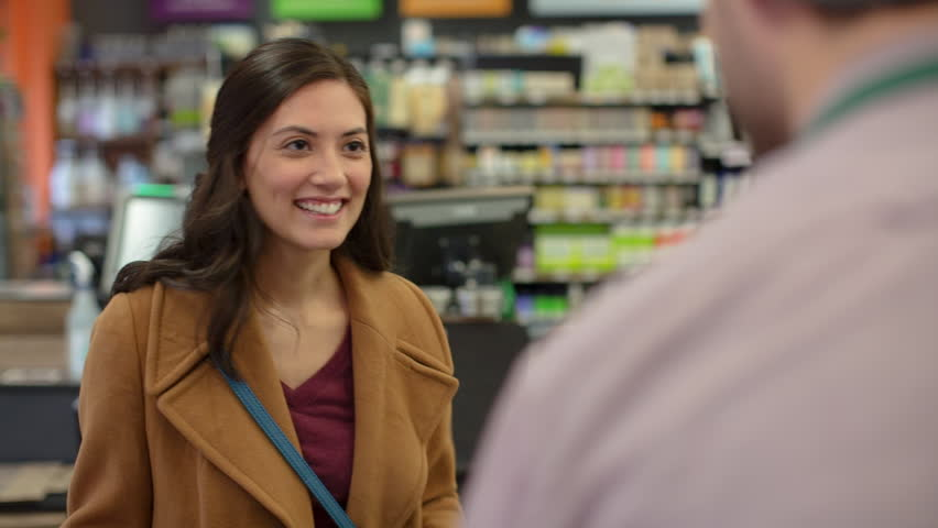 Handheld shot of female customer talking to worker at checkout counter in store | Shutterstock HD Video #1014999673