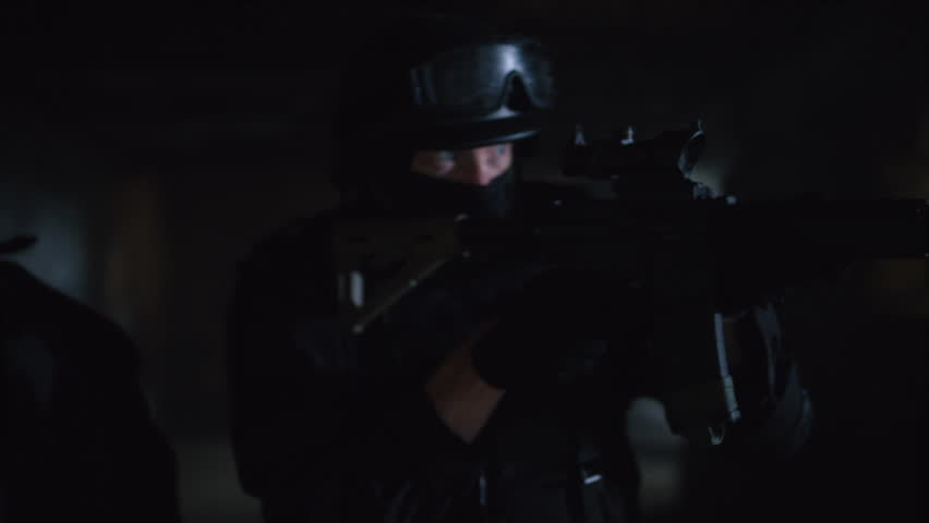 Three members of a SWAT team investigating a dark warehouse with flashlights and guns. Shot with a RED camera. 4k footage. | Shutterstock HD Video #1015002913