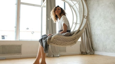 Young European girl in a linen dress swings in a hammock-swing in a loft apartment against the backdrop of a large window. Beautiful woman resting in a hammock chair