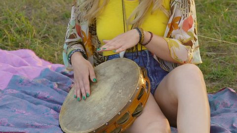 young blond hippie woman sitting on grass in park at sunset. Warm summer day and soft backlight. happy woman playing the tambourine and singing.
