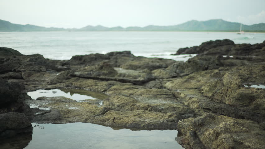 Close-up of small waves breaking over rocks on Costa Rica shoreline. Coastal rock formations on tropical beach. 4k