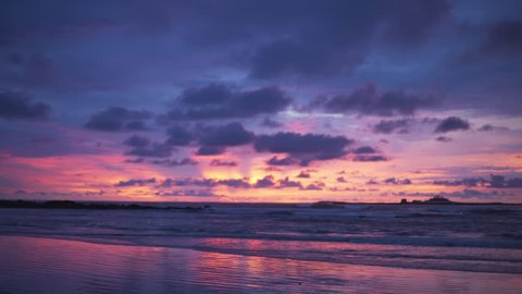 Out of focus background plate of orange, purple and blue sunset on the beach in Costa Rica for compositing or keying. Blurred or defocused shot of ocean sun set for green screen composite. 4k