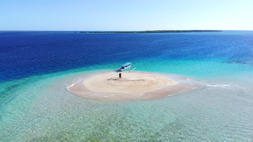 Epic shot of a couple on a little island surrounded by clear crystal blue water in Lombok, Indonesia. Shot in 4k. | Shutterstock HD Video #1015023853