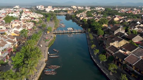 Aerial drone cinematic footage of the town of Hoian in Vietnam, South East Asia, with fishing boats and reflective water in the canal. Hoian is a very popular tourism destination in Vietnam .