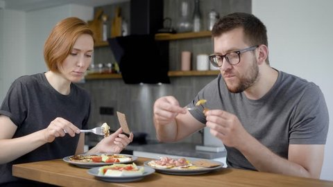 man and woman are having breakfast in kitchen of their home in morning, taking scrambled eggs