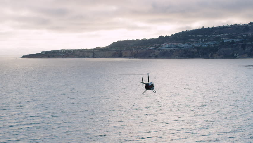 Aerial view of helicopter flying over the pacific ocean on a cloudy day. Shot of coast of Los Angeles, California. Shot with a RED camera. 4k footage.