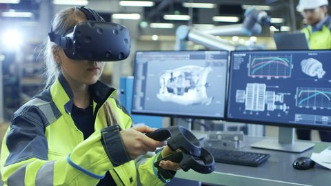 Factory: Female Industrial Engineer Wearing Virtual Reality Headset and Holding Controllers, She Uses VR technology for Industrial Design, Development in CAD Software.