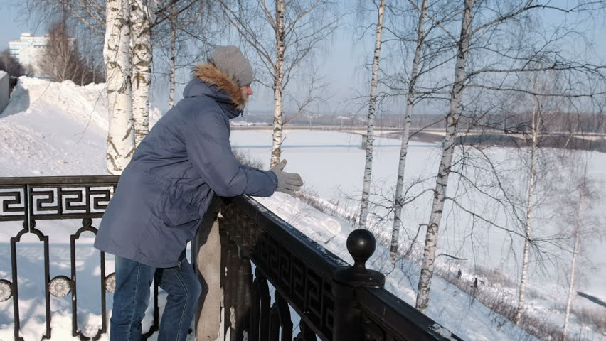 Man in blue down jacket with fur hood stands at the fence And look around in the winter Park.