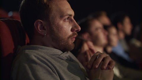 Young guy get scared while watching horror film. Man watch scary movie at cinema. Close up of people watching horror film. Spectators flinching at horror movie in cinema in slow motion
