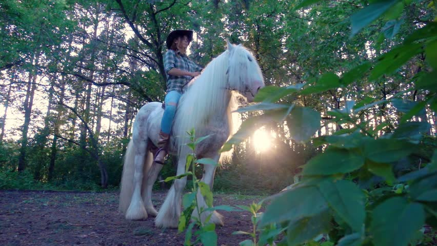 Young girl in cowboy hat riding a white horse. The stallion rises to his hind legs.