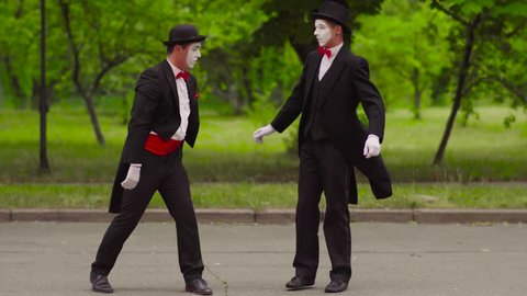 Two funny mimes do performance in the park