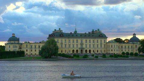 Drottningholm, Sweden - AUGUST 15, 2018: A man in a rowboat by Drottningholm Palace, Stockholm, Sweden.