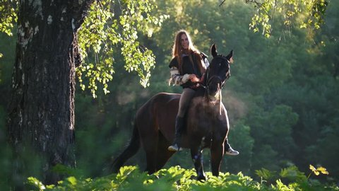 Horsewoman wearing jockeys on the background of green forest, early in the morning, gets off her horse