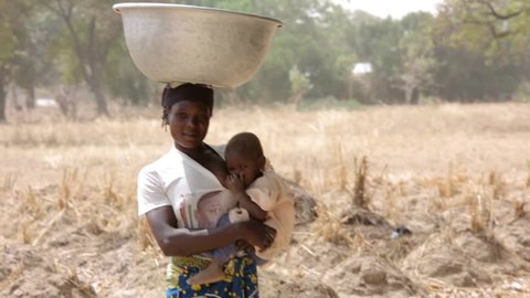 Sahel, Ghana - 2016: African woman carries a bowl on her head while holding her baby.