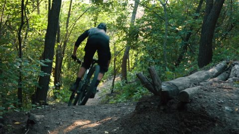 mountain biker rushes along road in forest, slow motion