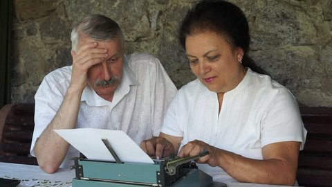 senior couple writing traditional mail by typewriter. woman typing and man sitting and thinking about story