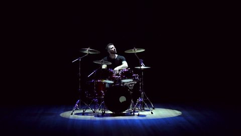 A young musician drummer plays on stage on a drum set on a black background with the light of a blue and white spotlight.