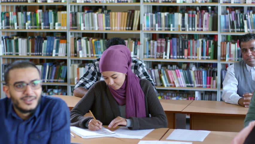 Tilt down of young middle eastern woman in hijab writing in notebook at desk in public library while studying language with group of migrants