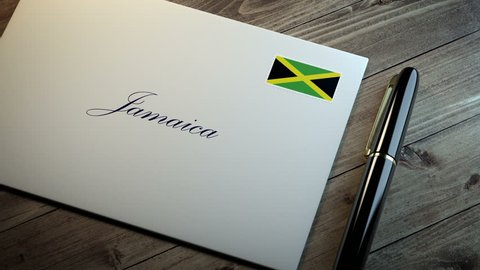 Country name written on a card or envelope in cursive font with a sleek pen on a wooden table surface under beautiful classy light. Stamp in the corner shows the flag of Jamaica